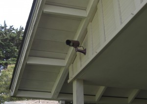 The well placed camera is mounted on a wall that can accommodate the cable while being visible and having a clear view of the street